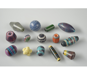 Trade Beads – from layered textile threads soaked in resin and then carved