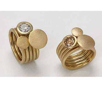 Stacking in rings in 18ct yellow gold set with white and cognac diamonds