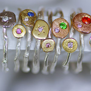 A selection of Rose Root rings in silver and gold with precious gems